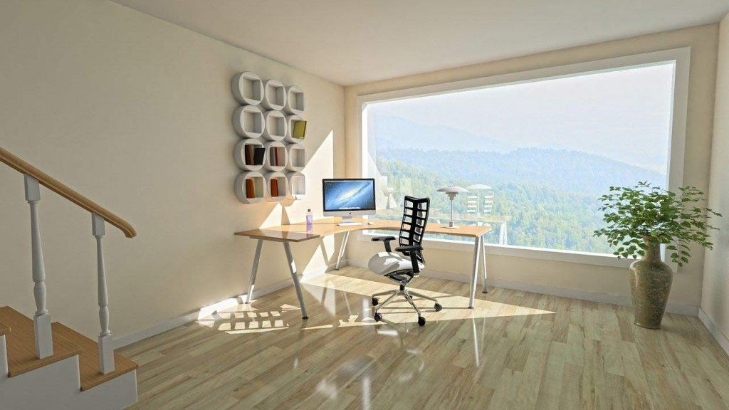 working from home office desk with window overlooking mountain landscape