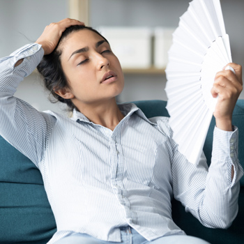 woman in uncomfortable summer heat without home insulation to keep cool air inside
